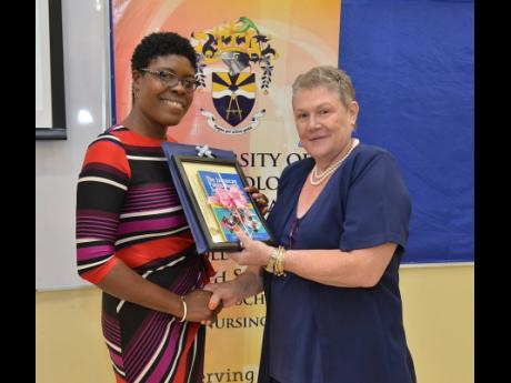 Dr Adella Campbell (left), head of the Caribbean School of Nursing at the University of Technology Jamaica, presents a book and a plaque to Dr Denise Eldemire-Shearer, senior lecturer in the Department of Community Health and Psychiatry, during the Fourth Annual Biennial Nursing Conference held at UTech's St Andrew campus yesterday.