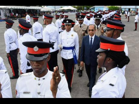 National Security Minister Dr Horace Chang (centre) conducts a review of 147 new police recruits graduating from the National Police College of Jamaica's Harman Barracks Campus.