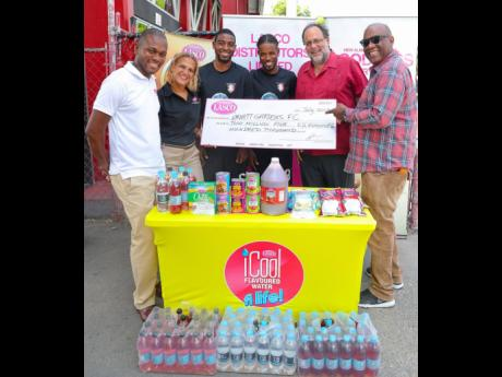 From left: LASCO Distributors Limited Marketing Manager Omar Palmer and Beverage Marketing Manager Danielle Cunningham present a $2.5-million cheque to Arnett Gardens Football Club midfielder Ricardo Oldham, and defender Lamard Neil, solidifying LASCO's support of the club's preseason preparations, on Thursday, July 25, 2019, in Arnett Gardens. Joining the proceedings are Member of Parliament for South St Andrew and Chairman of Arnett Gardens FC Mark Golding and the club's general manager, Peter Thelwell.