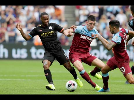Manchester City's Raheem Sterling vies for the ball with West Ham's Declan Rice (centre), and Manuel Lanzini (right) during the English Premier League football match between West Ham United and Manchester City at London stadium in London yesterday.