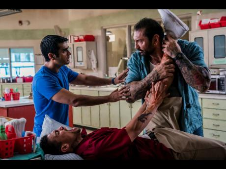 This image released by 20th Century Fox shows Dave Bautista (right) and Kumail Nanjiani (standing at left) in a scene from 'Stuber'.