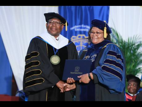 Northern Caribbean University President Dr Lincoln Edwards (left) presents Kay Dunkley with her Doctor of Philosophy in Education degree at the institution's Commencement Ceremony held on Sunday, August 11. The Graduating Class of 2019 totalled 506.