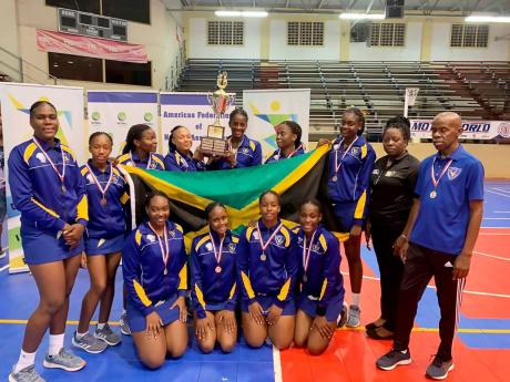 Members and support staff of the Gaynstead High School netball team pose with their trophy after capturing the Americas Federation of Netball Association Champion of Champions title in St Maarten.
