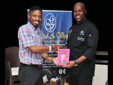 Bertland Hope (left), son of Professor Donna Hope, presents a copy of his mother's book, 'Chicken Back Gravy and Such Delights', to executive chef and host Dennis McIntosh during the book's launch at the Grand-A-View Restaurant in Montego Bay recently.