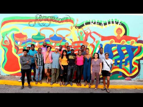 Artists in front of the augmented-reality mural in Kingston.