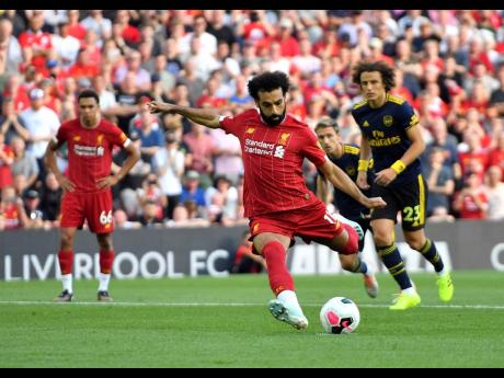 Liverpool's Mohamed Salah scores his side's second goal of the game from the penalty spot during their English Premier League match against Arsenal at Anfield, Liverpool, yesterday.