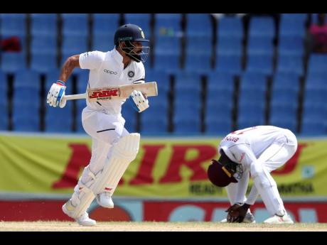 India's captain Virat Kohli (left) scores runs against the Windies as wicketkeeper Shai Hope hangs his head in frustration during day three of the first Test match at the Sir Vivian Richards cricket ground in North Sound, Antigua and Barbuda, yesterday.
