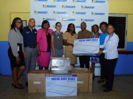 Staff at the Seaview Gardens Health Centre accepting much-needed new equipment from Massy Group.