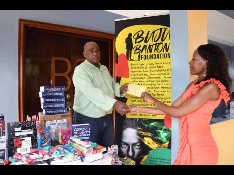 Administrator of the Mount Olivet Boys' Home Patrick Newman hands a thank-you letter to Rosemary Duncan of the Buju Banton Foundation.