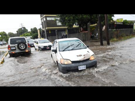 Motorists slowly traverse a flooded Maxfield Avenue in St Andrew on Monday as heavy rainfall inundated several Corporate Area roads.