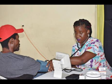 Sherry-Gay Campbell Chung, a community health aide stationed at the Port Maria Health Centre, checks the blood pressure of a senior citizen who turned out during Caribbean Wellness Day.