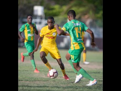 Clive Beckford of Charlie Smith (left) goes on the attack against Vindiesel Isaacs of Kingston High School in their ISSA/Digicel Manning Cup fixture played at Breezy Castle yesterday. The game ended 1-1.