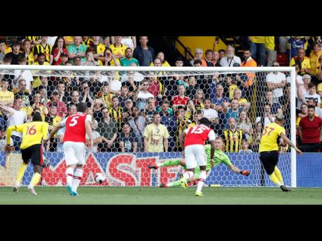 Watford's Roberto Pereyra (right) scores his side's second goal from the penalty spot during the English Premier League against Arsenal at the Vicarage Road stadium in Watford, near London, yesterday.