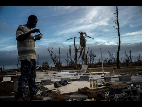 Jeffrey Roberts, 49, eats while searching, last Saturday, through the rubble of his relatives' home that was destroyed by Hurricane Dorian in Pelican Point, Grand Bahama, Bahamas. The death toll from the hurricane stands at 50 and the number of missing at an alarming 1,300 people, although officials caution the list is preliminary and many people could just be unable to connect with loved ones.