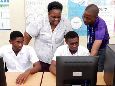 Tacky High School student Shaquiel Williams (on computer) gets instructions from IT teacher Lois Small (second left) and Food For the Poor IT specialist Ryan Francis (right), as he tries out one of the new computers..