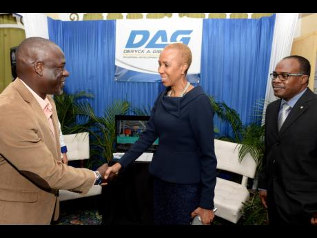 Science, Energy and Technology Minister Fayval Williams (centre) greets Vice President, Marketing, Jamaica Institution of Engineers (JIE), Godfrey Boyd, during the JIE's Engineers' Week Conference at The Knutsford Court Hotel in New Kingston on Tuesday.  Sharing  in the moment is JIE President Christopher Hamilton.
