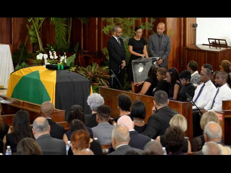 From left: Children of the late Dr Kenneth Baugh, Gregory, Melanie, and Warren, read a remembrance during the thanksgiving service for the former politician at the University Chapel in Mona, St Andrew, yesterday.