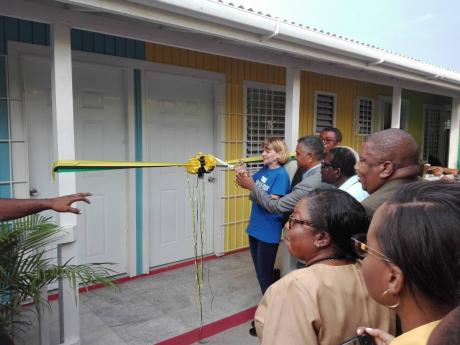 Denise DiBiase is assisted by Michael Stern, deputy board chairman of the Southern Regional Health Authority, as she cuts the ribbon to mark the official opening of the Rock River Health Centre in Clarendon.