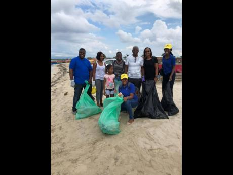UNESCO youth ambassadors pose with Pearnel Charles Jr (second right) during a recent beach clean-up.