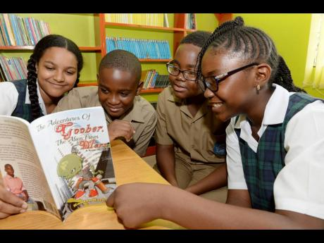 Young author Kanton Hardy (second left) and fellow students at Meadowbrook Preparatory School in St Andrew peruse his book, 'The Adventures of Goober: The Alien from Mars', at the school recently.