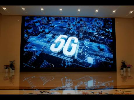 In this March 6, 2019 photo, a 5G logo is displayed on a screen outside the showroom at Huawei campus in Shenzhen city in China's Guangdong province.