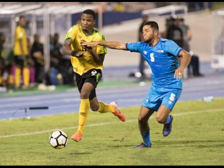 Jamaica's Alvas Powell (left) on the offensive against Aruba's Noah Harms in their Concacaf Nations League B game at the National Stadium in Kingston, Jamaica, on Saturday, October 12, 2019.