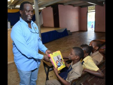 KSAC councillor Patrick Roberts hands over books to Drewsland Primary School.