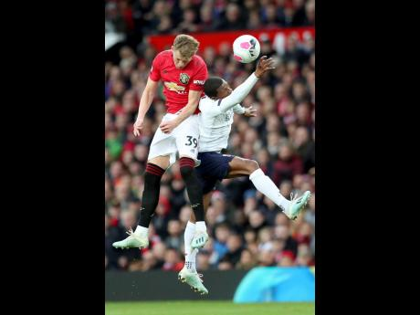 Manchester United's Scott McTominay (left) jumps for a header with Liverpool's Sadio Mane during their English Premier League match at Old Trafford in Manchester, England yesterday.