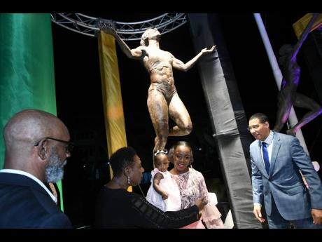 Decorated Jamaican athlete Veronica Campbell-Brown holds her daughter, Avianna Amora Brown, as she chats with Sport Minister Olivia Grange, Prime Minister Andrew Holness (right) and sculptor Basil Watson (left) after the unveiling of a statue in honour of the Olympian at Statue Park inside Independence Park, St Andrew, yesterday.
