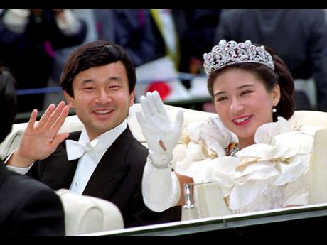 In this June 9, 1993, file photo, then Crown Prince Naruhito and Crown Princess Masako wave during their wedding parade in Tokyo. Japan is abuzz ahead of today's ceremony marking Emperor Naruhito's ascension to the Chrysanthemum Throne.