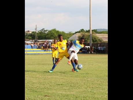 Sydney Pagon High School's Christan White (left) and St Elizabeth Technical High School's (STETHS) Rohan Brown (right) tussle for the ball during their ISSA/WATA daCosta Cup match at the STETHS Sports Complex on Wednesday, September 18, 2019.