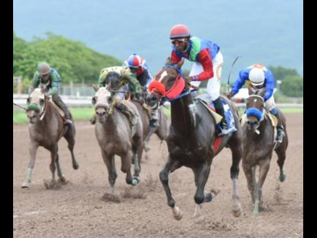 SUPERLUMINAL (second right), ridden by Omar Walker, finishes ahead of BRUCE WAYNE and DONTAE to take the Fontainbleu Trophy at Caymanas Park yesterday.