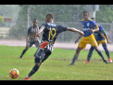 Jamaica College's Rajae Lawrence takes a shot on goal during their ISSA/Digicel Manning Cup game against José Martí High School in heavy rainfall at the Ashenheim Stadium on Saturday, September 7, 2019.
