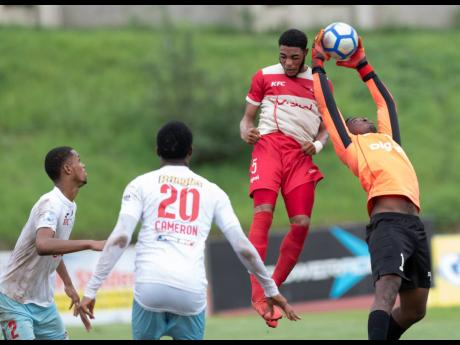 Shaid McLean (left) and Naeem Cameron look on as goalkeeper Orville Smikle (right) of St George's College snatches the ball ahead of Mona High School's Loloxley Reid (second right) in their second-round first-leg ISSA/Digicel Manning Cup fixture at Stadium East yesterday.