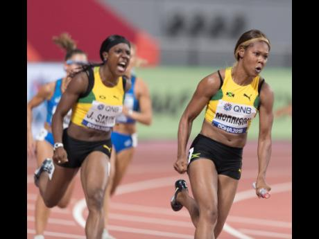 Jamaica's Jonielle Smith (left) urges on teammate Natasha Morrison, who powers her way through the anchor leg of their women's 4x100m relay heat, at the IAAF World Championships at the Khalifa International Stadium in Doha, Qatar, on Friday, October 4.