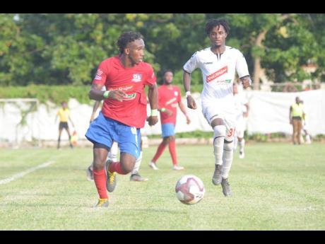 Dunbeholden forward Demario Phillips (left) dribbles as UWI defender Damano Solomon approaches to close him down during their Red Stripe Premier League fixture at the Royal Lakes field in St Catherine yesterday.