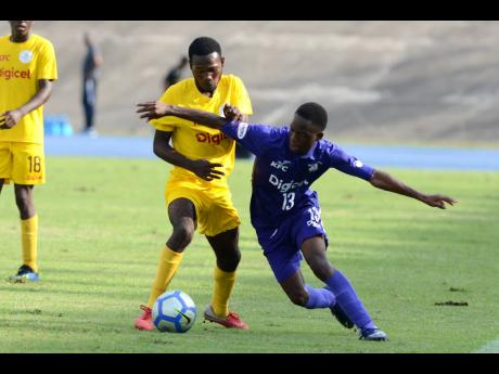 Dwayne Atkinson of Kingston College (right) dribbles away from  Charlie Smith's Oshane Samuels in their ISSA-Digicel Manning Cup encounter at the National Stadium, yesterday. Kingston College won the game 5-0.