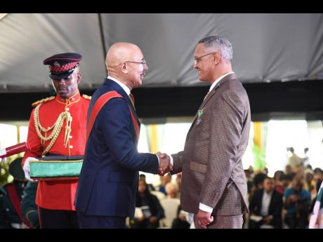 Governor General Sir Patrick Allen (centre) presents the Badge of Honour for Long and Faithful Service to the Reverend Paul Neil, for service to Religion and Community Service, at the National Honours and Awards Ceremony at King's House on October 21.