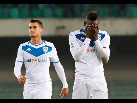 Brescia's Mario Balotelli (right) reacts at the end of the Italian Serie A match against Verona and Brescia at the Bentegodi stadium in Verona yesterday. Verona supporters' racist chants upset the Italian bomber who also scored one goal in his team's 2-1 loss.