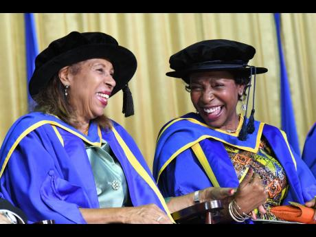 Molly Rhone (left) and former US Congresswoman Yvette Clarke share a laugh after they were conferred with honorary degrees at the University of Technology, Jamaica's graduation ceremony at its Papine, St Andrew, campus yesterday.