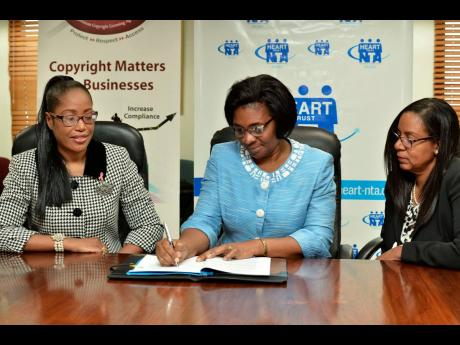 Dr Janet Dyer (centre), managing director of the HEART Trust/NTA, signs the Tertiary Licensing Agreement between the HEART Trust/NTA and the Jamaican Copyright Licensing Agency (JAMCOPY) on Thursday, October 31. Looking on are JAMCOPY General Manager Carol Newman (left) and Dianne Daley McClure, chairman, JAMCOPY. This signing brings to 34, the number of JAMCOPY's compliant institutions.