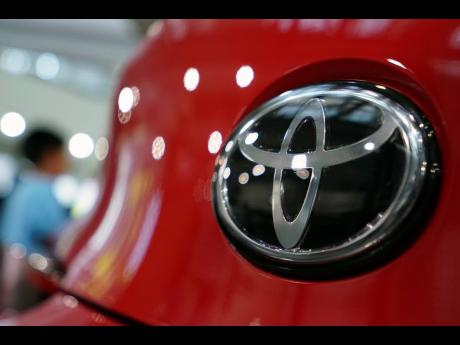 AP In this August 2, 2019, file photo, people walk by the logo of Toyota at a showroom in Tokyo.