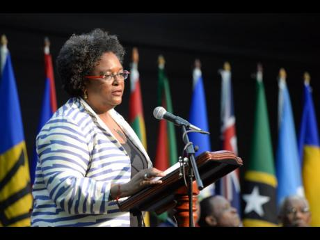 Flags of Caricom member states form a backdrop for Prime Minister of Barbados Mia Mottley as she addressed the 39th Caricom Heads of Government Meeting held in Montego Bay in July 2018.