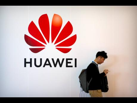 In this October 31, 2019 file photo, a man uses his smartphone as he stands near a billboard for Chinese technology firm Huawei at the PT Expo in Beijing.