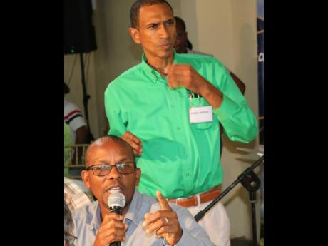 CEO of the Sugar Industry Authority, George Callaghan, answering questions at the annual general meeting of the All-Island Jamaica Cane Farmers Association yesterday, while manager Nigel Myrie listens. Photo by Christopher Serju