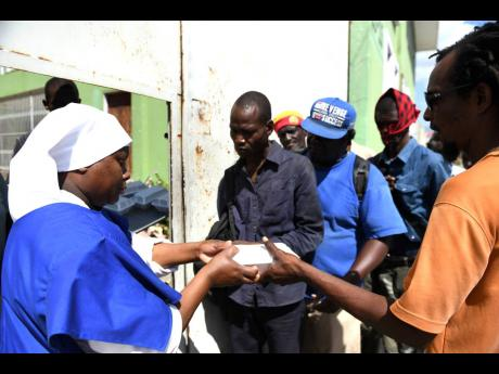 Sister Pauline Rukunyi of Kenya hands out boxed lunches to men waiting on the outside of the Missionaries of the poor Sisters'  holy innocents centre at Heroes Circle.
