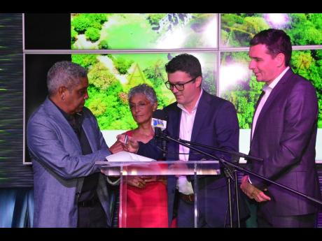 Keith Russell, chairman of Amaterra Group, and his wife, Paula, director of Amaterra Group, sign the agreement making Marriott International the operators of their 800-room Trelawny resort. Bojan Kumer (second right), vice-president of Marriott Hotel Development Caribbean, and Laurent de Kousemaeker, chief development officer, Caribbean and Latin America, await their turn to sign the document.