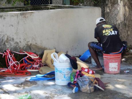 Groom Mario Skeen working in the stables area at Caymanas Park last week.
