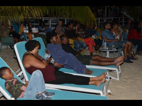 Photos by Janet Silvera  Locals and tourists enjoy Jamaican movies outdoors in Negril recently.