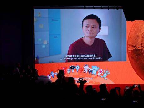 A screen shows footage of Alibaba Group co-founder Jack Ma during the Alibaba Group's listing ceremony at the Hong Kong Stock Exchange in Hong Kong, Tuesday, November 26.